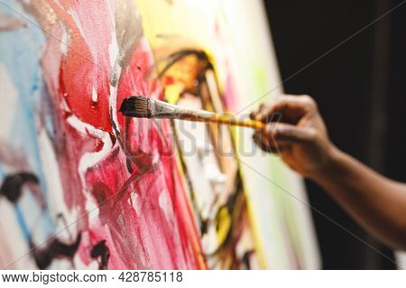 Close up of african american male painter at work painting on canvas in art studio. creation and inspiration at an artists painting studio.