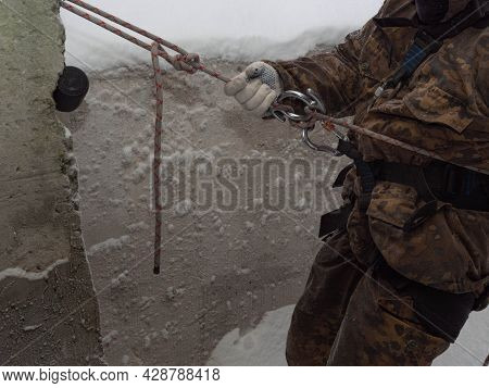 A Military Mountaineering Instructor Teaches Climbing Knots From A Rope With A Carbine And