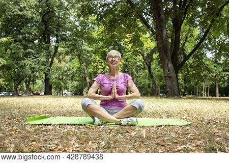 Senior Caucasian Woman Enjoys Doing Yoga Exercise.