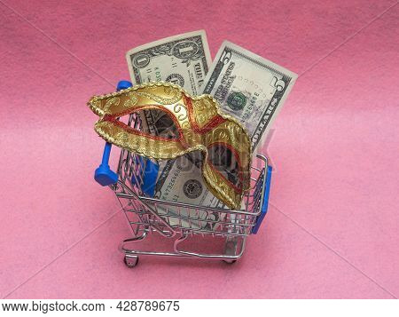 A Traditional Venetian Golden Carnival Mask With Money (dollar Cuppures) In A Toy Shopping Cart On A