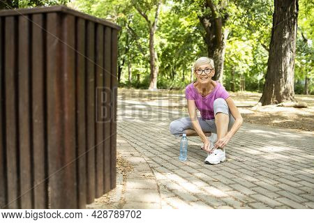 Portrait Of Senior Caucasian Woman Tying Her Shoelace Before Jogging In The Park.