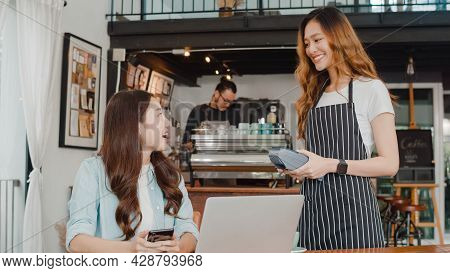 Young Asian Freelance Women Pay Contactless At Coffee Shop. Asian Happy Girl Barista Waiter Wear Gra