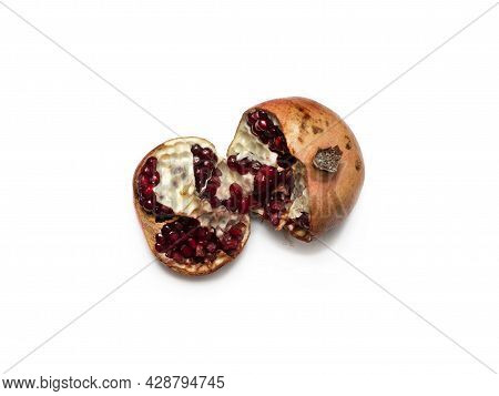 Spoiled, Unhealthy, Open Red Pomegranate With Seeds Falling Out. Concept Of Expired Food Products. C