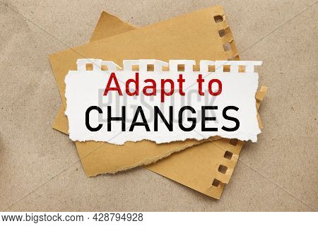 Adapt To Changes, White Torn Paper On Brown Torn Paper Background. Craft Background