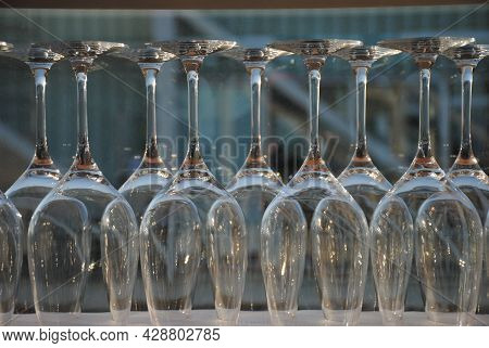 Wine And Cocktail Glasses Hanging Upside Down In Row