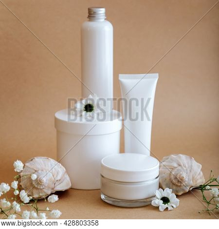 Set Natural Beauty Cosmetic Skincare Products With Flowers Sea Shells On Beige Background. White Kit