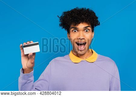 Astonished African American Man In Violet Pullover Showing Credit Card Isolated On Blue
