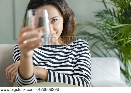 Young Woman Smiling While Looking At The Camera Through The Glass Of Water. Health Benefits Of Drink