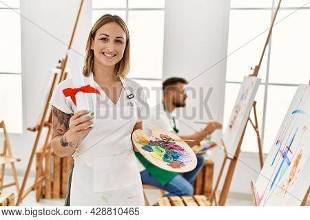 Young hispanic couple drawing at studio. Girl smiling happy and holding art diploma degree.