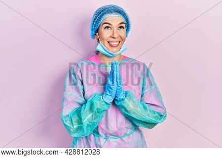 Young brunette woman wearing surgeon uniform and medical mask begging and praying with hands together with hope expression on face very emotional and worried. begging.