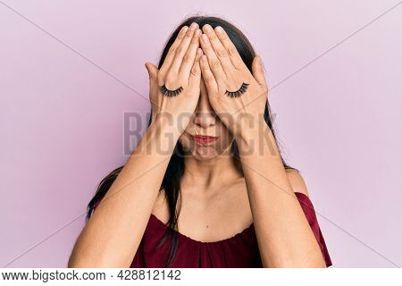 Young hispanic woman covering eyes with hands and fake lashes puffing cheeks with funny face. mouth inflated with air, catching air.