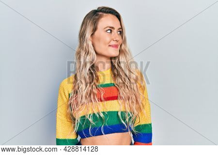 Beautiful young blonde woman wearing colored sweater smiling looking to the side and staring away thinking.