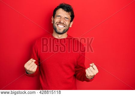 Handsome man with beard wearing casual red sweater very happy and excited doing winner gesture with arms raised, smiling and screaming for success. celebration concept.