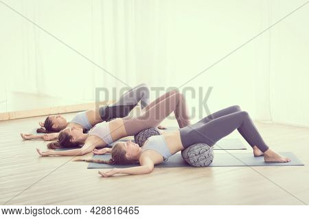 Restorative Yoga With A Bolster. Group Of Three Young Sporty Attractive Women In Yoga Studio, Lying