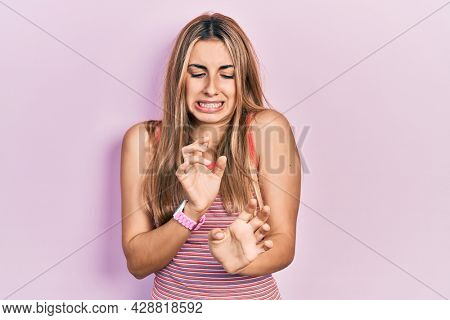 Beautiful hispanic woman wearing casual summer t shirt disgusted expression, displeased and fearful doing disgust face because aversion reaction.