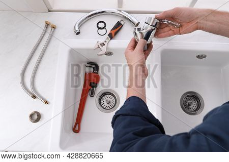Professional Plumber Fixing Water Tap In Kitchen, Top View