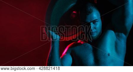 Portrait of a strong healthy handsome athletic man holding a large iron disk on his shoulders in multicolour red and blue lighting. Male beauty concept. Bodybuilding, weightlifting.
