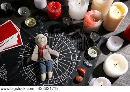 Voodoo Doll Pierced With Needle Surrounded By Ceremonial Items On Table. Curse Ceremony
