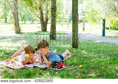 Two Boys Lie On A Blanket In A Green Park. Children Read A Book Lying On The Ground, In The Park. Ch