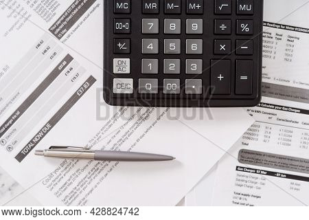 Top View Of Black Calculator With Pen Laying On Various Invoices And Monthly Utility Bills On Table