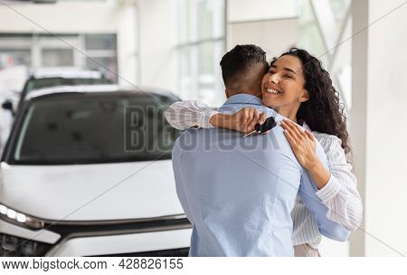 Ecstatic Curly Woman With Key From Car Hugging Husband