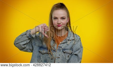 Upset Pretty Stylish Teen Girl In Denim Jacket Showing Thumbs Down Sign Gesture, Expressing Disconte