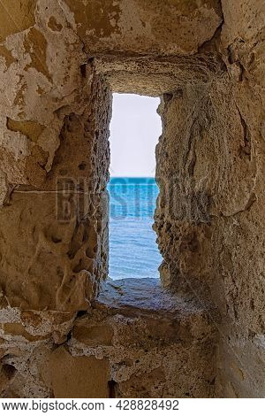 A View Of The Sea Through The Loophole Of A Medieval Fort In The Southern Part Of The Finikoudes Emb