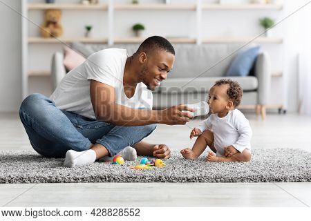 Caring Young Black Dad Giving Water To His Little Baby At Home