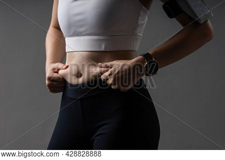 Closeup Body Of Woman In Sportswear Healthy Exercise With Fat On Belly Problem. Cellulite On Fat Bel