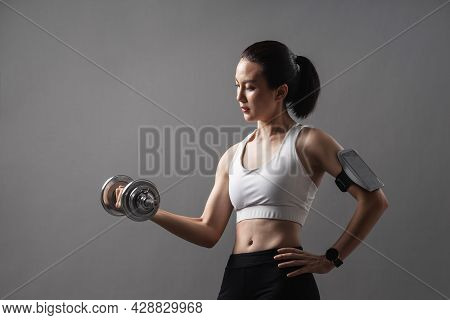 Portrait Athlete Asian Active Woman Workout With Dumbbell Weightlifting In Studio Grey Background. Y