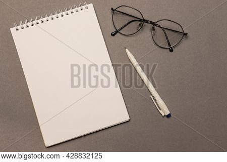 A Blank Sheet Of Spiral Notebook Paper, Glasses And A Pen On A Gray Background, Top View. Business C