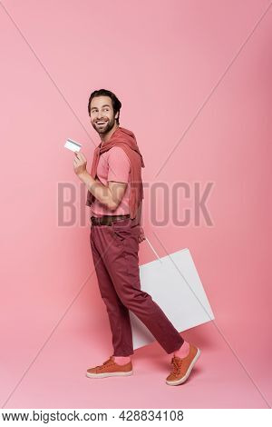 Full Length Of Shopaholic With Credit Card And Shopping Bag Walking On Pink Background