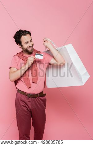 Brunette Shopaholic Holding Shopping Bag And Credit Card On Pink Background