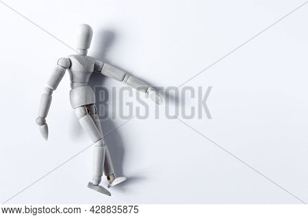 Abstract Figure Of A Wooden Man Lying On His Side On A Light Background. The Figure Of A Wooden Man