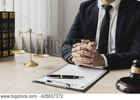 A Male Lawyer Sits In The Office Of His Law Firm, On A Table With A Scale Of Justice And A Hammer La