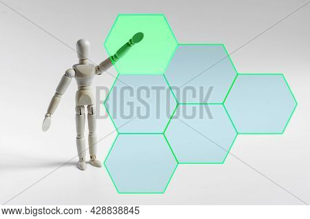 The Figure Of A Wooden Man Pointing With His Hand At An Interactive Panel. The Figure Of A Wooden Ma