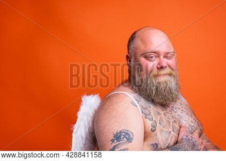 Fat Doubter Man With Beard , Tattoos And Wings Acts Like An Angel