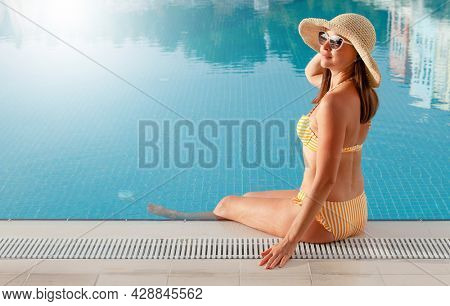 Woman relaxing in swimming pool on summer vacation. Hot sunny holiday concept