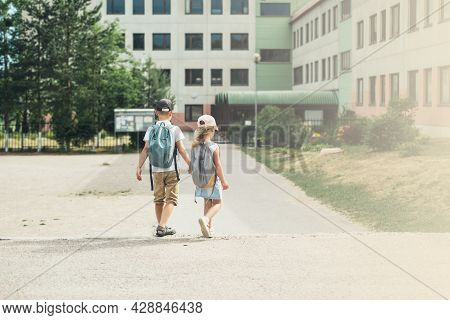 Boy And Girl, Elementary School Students, Walking To School With Bags Behind Their Backs. Students A
