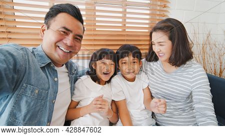 Young Happy Asian Family Talk To Selfie Point Of View Camera, Online Remote Video Call With Friend.
