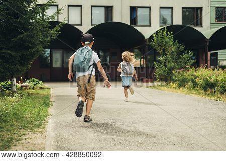 Two Caucasian Children, Boy And Girl, Running To School With Bags Behind Their Backs. Students Are R