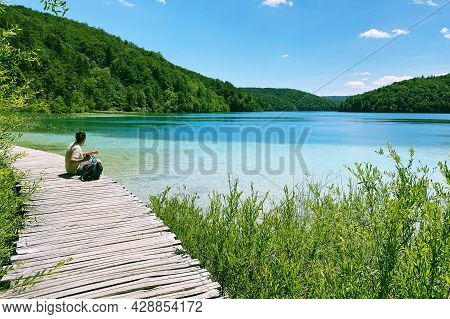 Tourist Relaxing In Nature. Summer Landscapes Along Lake In Traveling Journey. Wooden Vintage Bridge