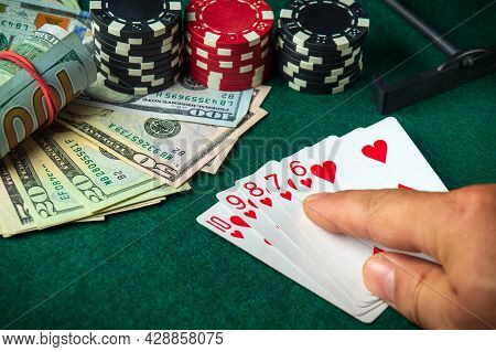 Player Points With His Finger At A Winning Straight Flush Combination In A Poker Game On A Table Wit