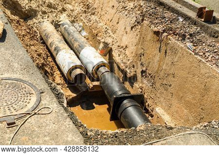 Water Pipes In Ground Pit Trench Ditch During Plumbing Under Construction Repairing. Repair Of A Wat