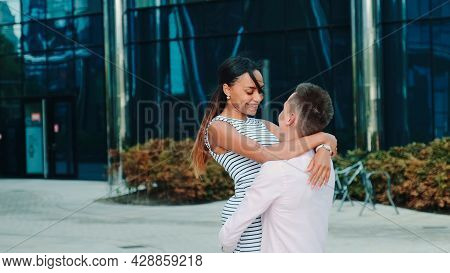 Multi-ethnic Couple In Love Spending Time Together In The Center Of The Big City. Man Holding Woman