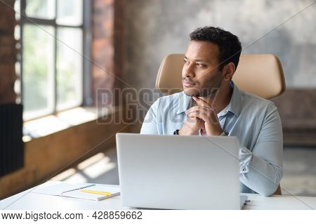 Serious Concentrated Clever Indian Freelancer Guy Using Laptop For Searching, Looking Away Lost In S