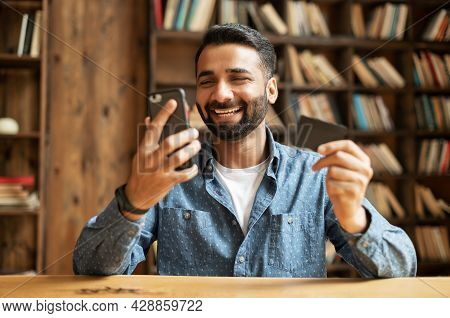 Overjoyed Happy Joyful Young Indian Man Paying Online With Credit Card, Using Smartphone App For Sho