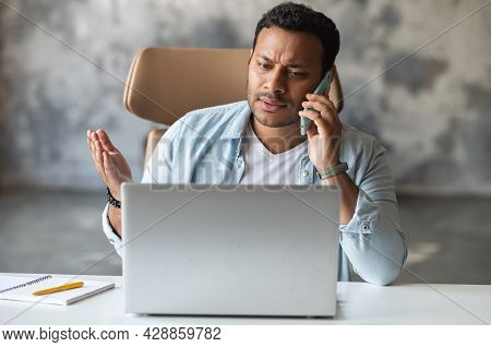Annoyed Indian Guy Talking On The Smartphone Sitting At The Office Desk With A Laptop, Receiving Som