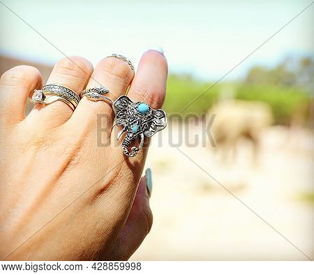 Graceful Female Hand With A Ring In The Shape Of An Elephant Reaches For Nature. Graceful Female Han