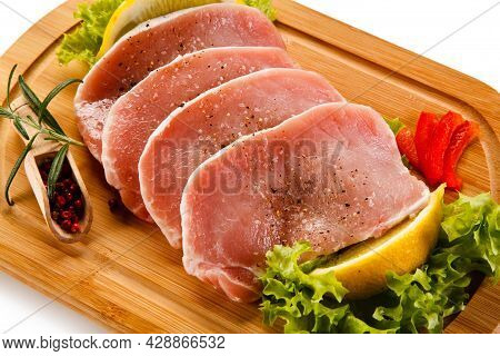 Fresh Raw Pork Meat On White Desk. Pork Chop With Red Onion And Roasting Meat. Food And Poultry Conc